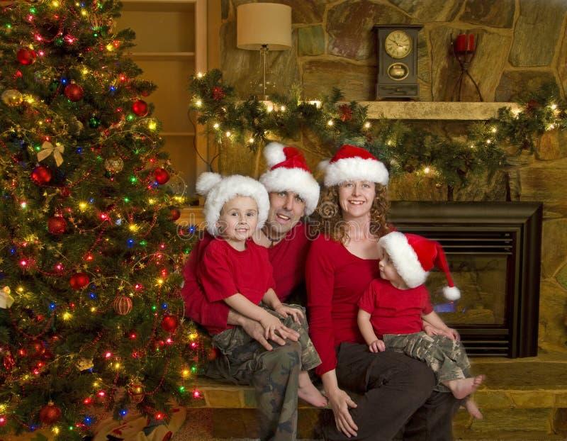 Familie sitzt neben Weihnachtsbaum lizenzfreies stockfoto