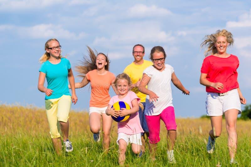 Familie speelbalspels op weide stock foto's