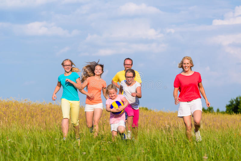 Familie speelbalspels op weide stock fotografie