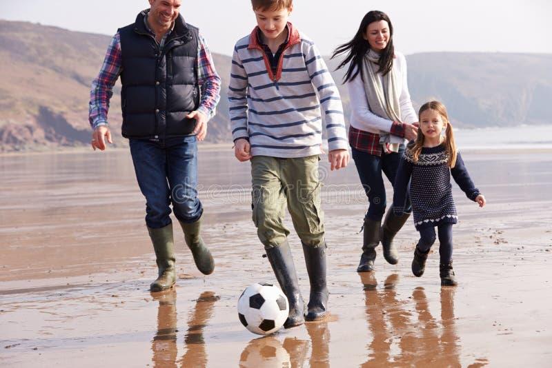 Familie Speelvoetbal op de Winterstrand royalty-vrije stock foto's