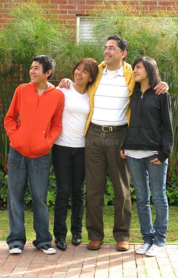 Familie steht auf Gras gegen Haus stockbild