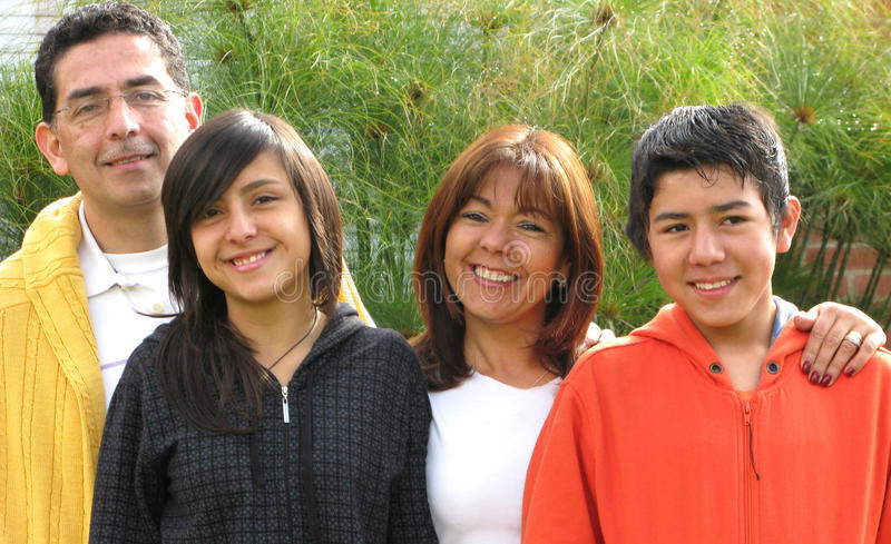 Familie steht auf Gras gegen Haus stockfotografie