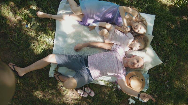 Familie steht im Park - Vater, Mutter und Tochter frühstücken Sie - Draufsicht still lizenzfreie stockfotografie