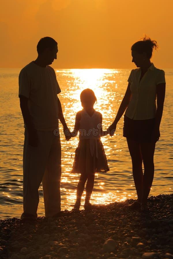 Familie tegen het polijsten van overzees. Ouders en dochter stock foto's