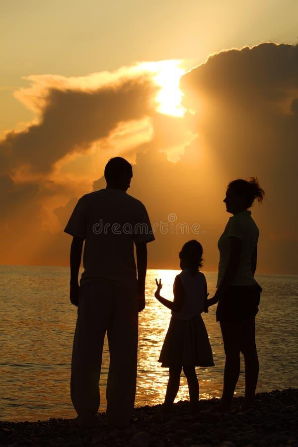 Familie tegen het polijsten van overzees. Ouders en dochter royalty-vrije stock foto's