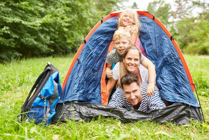 Familie in tent terwijl het kamperen op vakantie stock fotografie