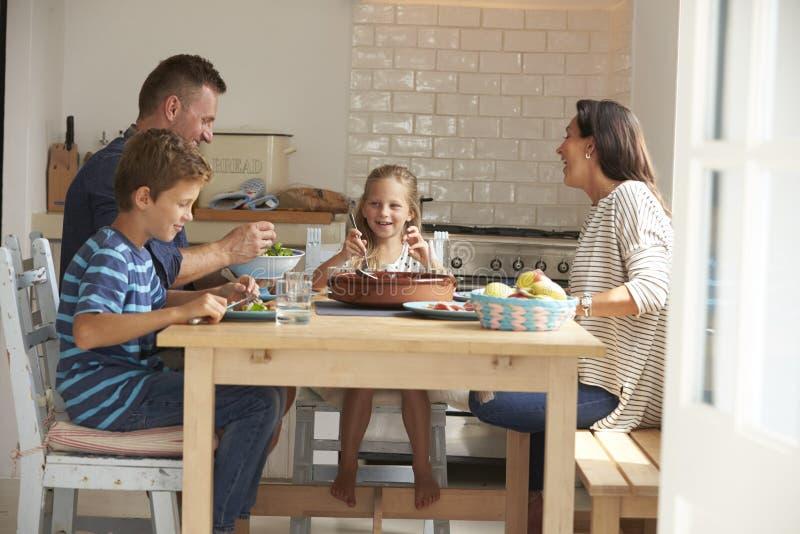 Familie thuis in samen het Eten van Maaltijd stock afbeelding