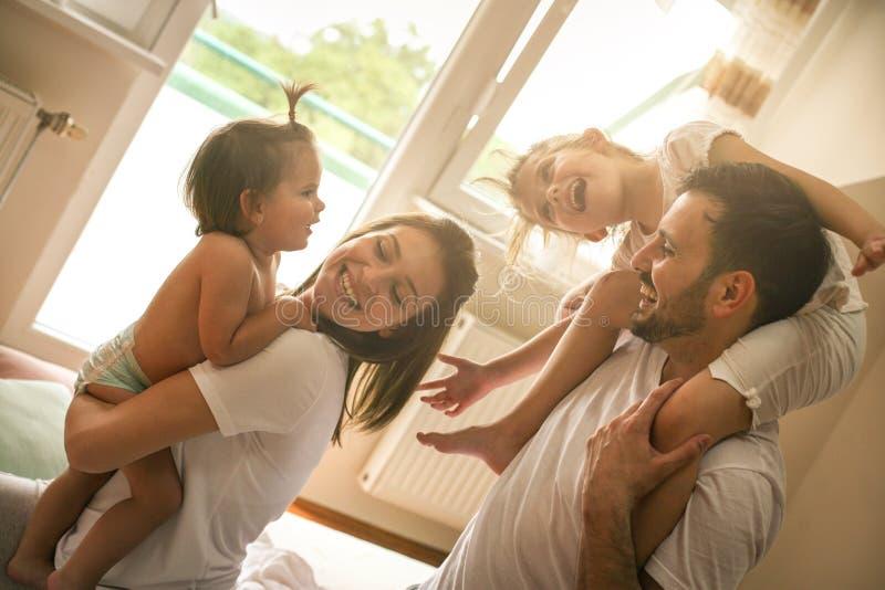 Familie thuis Vrolijke familie die pret met erfgenaamdochter hebben stock foto's