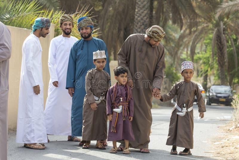 Familie in traditionele kleding bij een stuk speelgoed markt stock afbeelding