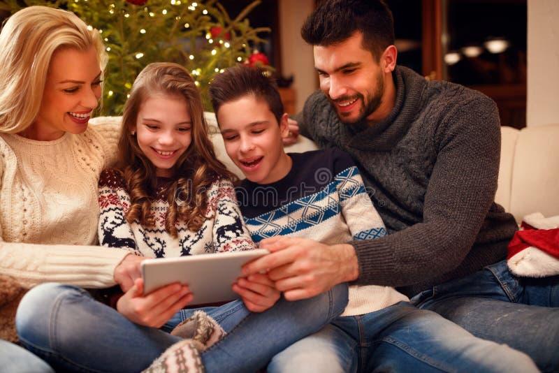 Familie trat um einen Weihnachtsbaum und mit Tablette zusammen stockbild