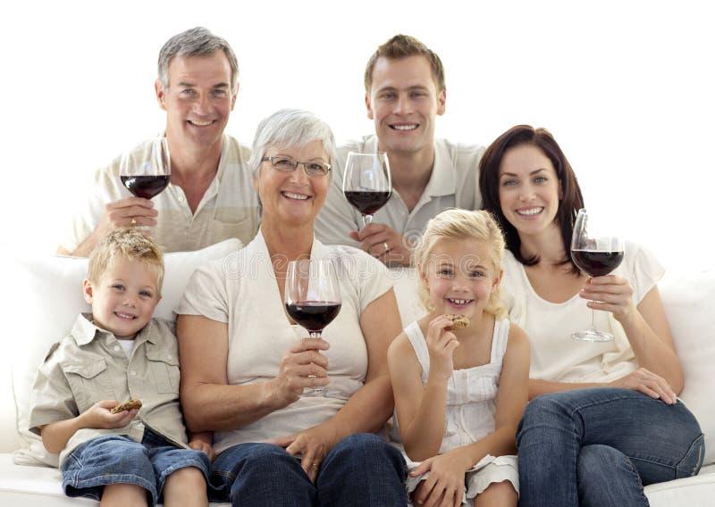 Familie in trinkendem Wein und im Essen des Wohnzimmers stockfotos