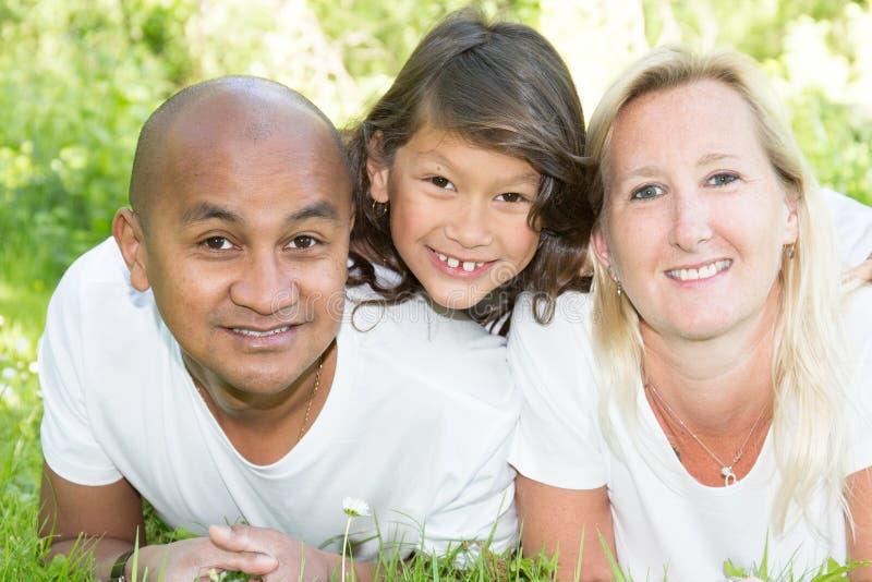 Familie tussen verschillende rassen met weinig kinddochter die op groene grastuin liggen stock fotografie