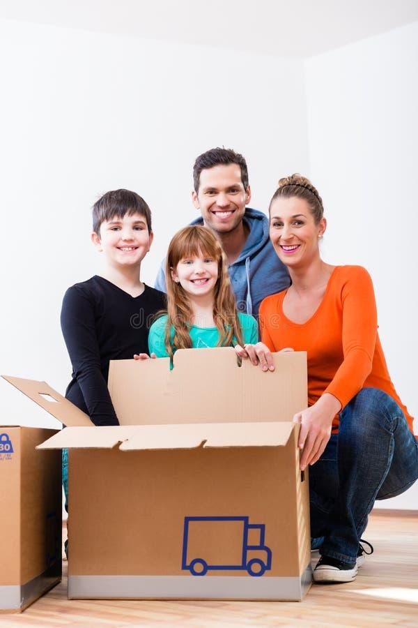 Familie uitpakkende bewegende dozen in nieuw huis royalty-vrije stock afbeelding