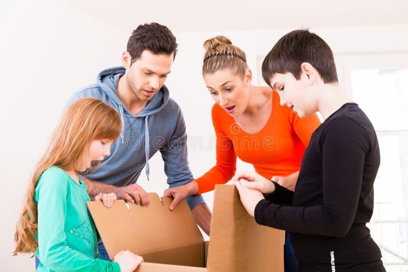 Familie uitpakkende bewegende dozen in nieuw huis royalty-vrije stock foto