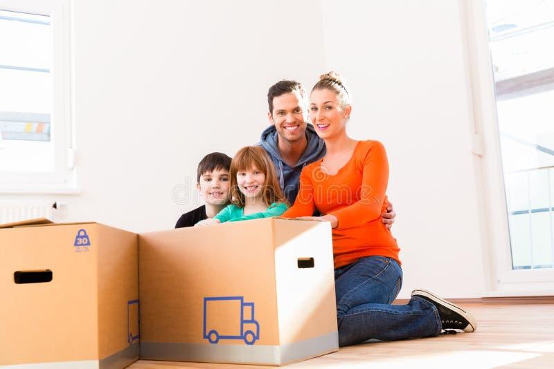 Familie uitpakkende bewegende dozen in nieuw huis stock fotografie