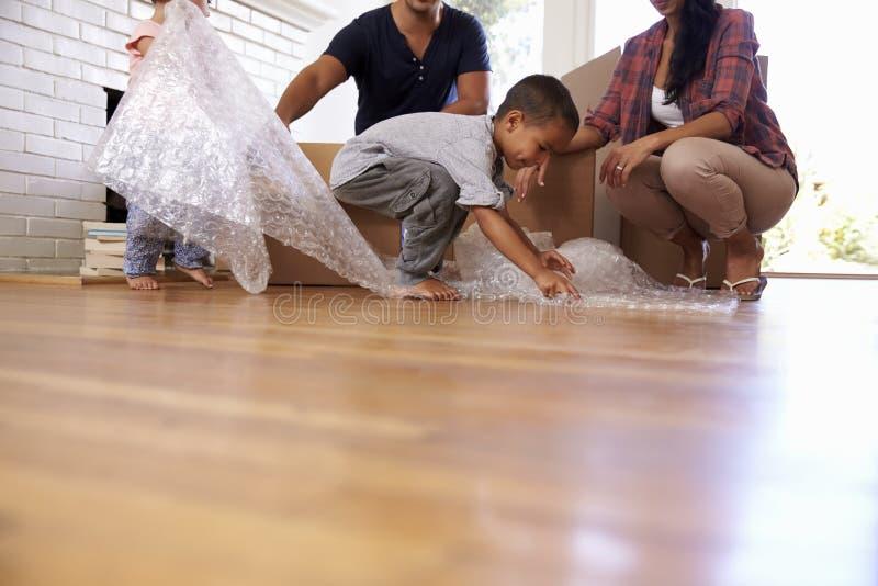 Familie Uitpakkende Dozen in Nieuw Huis bij het Bewegen van Dag stock foto's