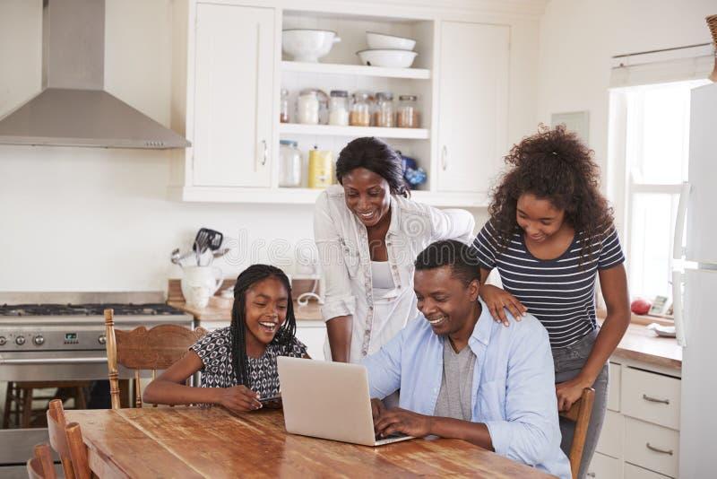 Familie um Küchentisch-Anmeldungs-Ferien auf Laptop zusammen stockbild