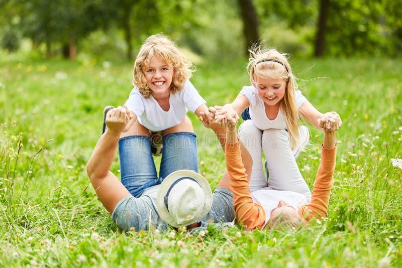 Familie und Kinder spielen auf einer Wiese lizenzfreies stockbild
