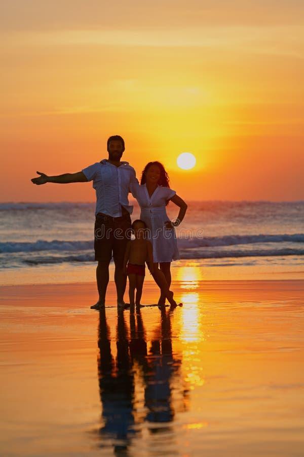Familie - vader, moeder, babygang op zonsondergangstrand stock afbeelding