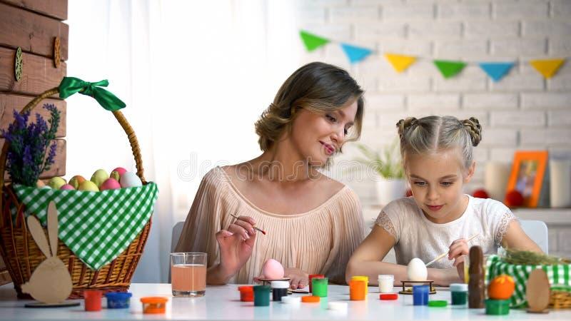 Familie van aanwezig kunst twee centrum en het leren om paaseieren, creativiteit te kleuren stock afbeelding