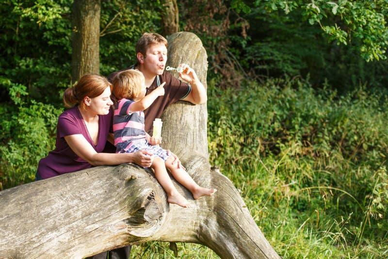 Familie van drie blazende zeepbels samen in de zomerbos royalty-vrije stock afbeeldingen