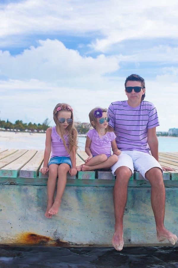 Familie van drie die bij het houten dok genieten zitten van royalty-vrije stock afbeeldingen
