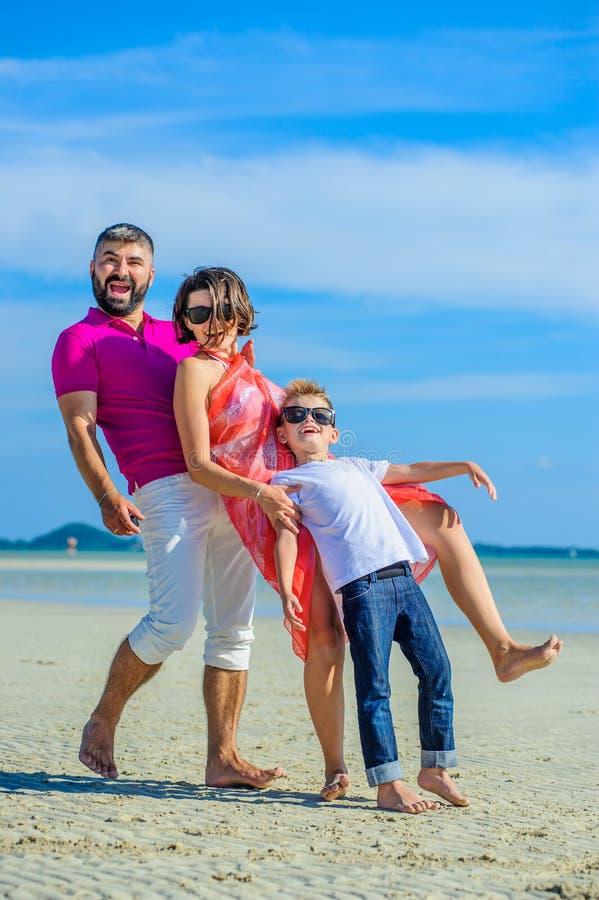 Familie van drie die langs het tropische strand, de lachende en enjoing tijd samen lopen royalty-vrije stock foto's