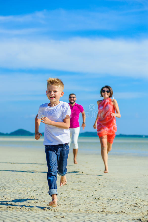 Familie van drie die langs het tropische strand, de lachende en enjoing tijd samen lopen stock afbeelding