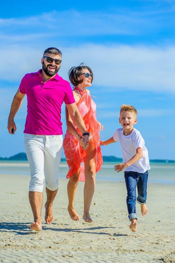 Familie van drie die langs het tropische strand, de lachende en enjoing tijd samen lopen stock fotografie