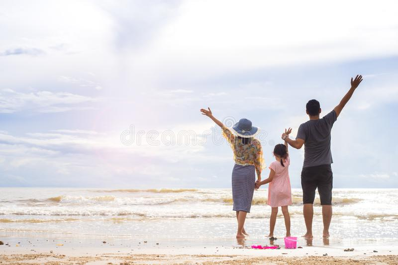 Familie van drie die pret op het strand hebben stock afbeelding