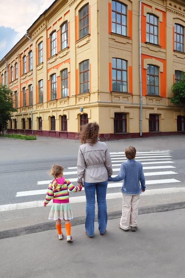 Familie van drie en de kruising van weg royalty-vrije stock afbeelding