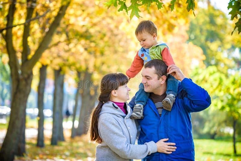 Familie van drie gangen in de de holdingshanden van het de herfstpark gelukkige vader dragende zoon met esdoornbladeren De moeder royalty-vrije stock afbeeldingen