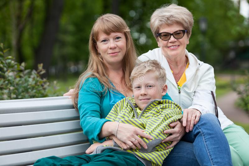 Familie van drie mensen die camerazitting bekijken op tuinbank samen in omhelzing, jonge jongen, volwassene en bejaarden stock afbeelding