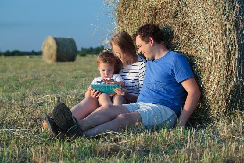 Familie van drie met stootkussen op het gebied met hooi stock afbeelding