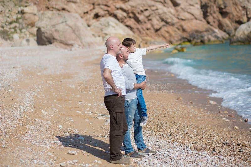Familie van grootvadervader en zoon op een rotsachtig strand op vakantie die van tijd samen genieten stock afbeelding