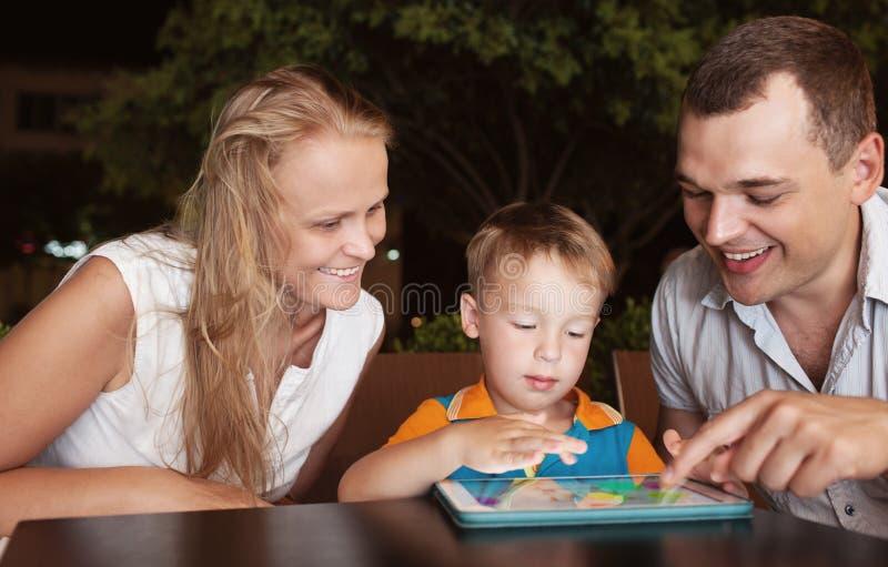 Familie van het besteden drie tijd in koffie met tablet stock afbeelding