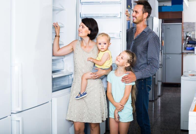 Familie van het winkelen vier nieuwe ijskast in de opslag van het huistoestel royalty-vrije stock afbeeldingen