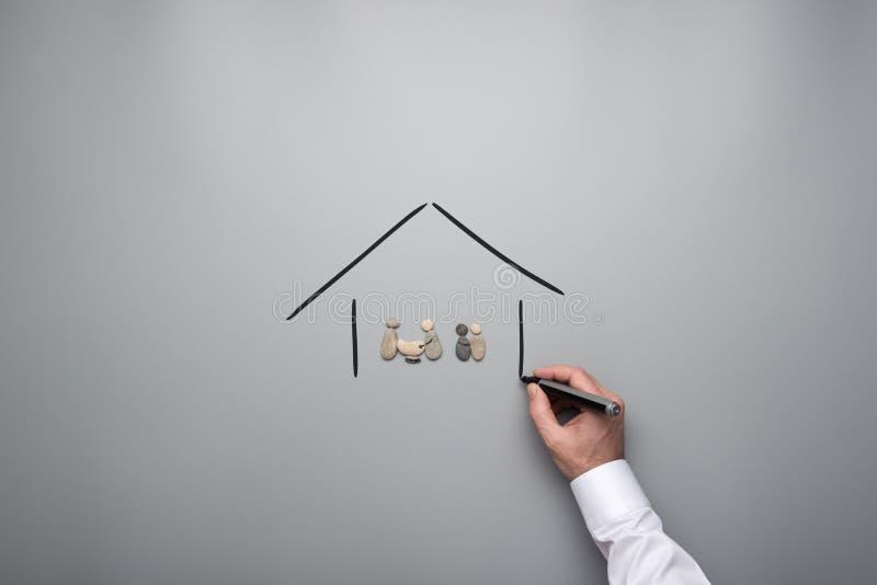 Familie van kiezelstenen in een hand getrokken huis wordt gemaakt dat stock afbeeldingen