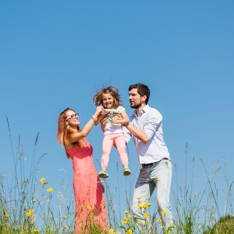 Familie van moeder, vader en kind op weide stock fotografie