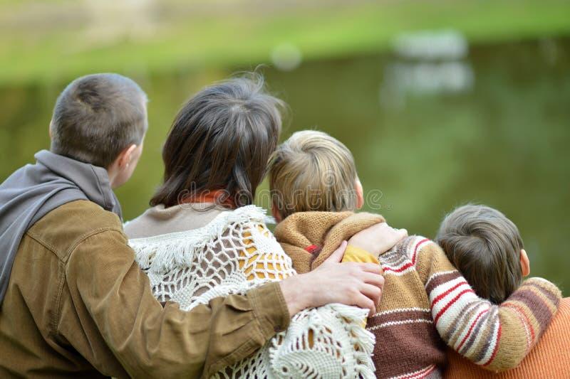 Familie van stellende zitting vier op gras royalty-vrije stock afbeeldingen