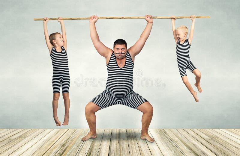 Familie van strongman De vader en twee zonen in uitstekende kostuums slepen de kabel De familie kijkt royalty-vrije stock foto's