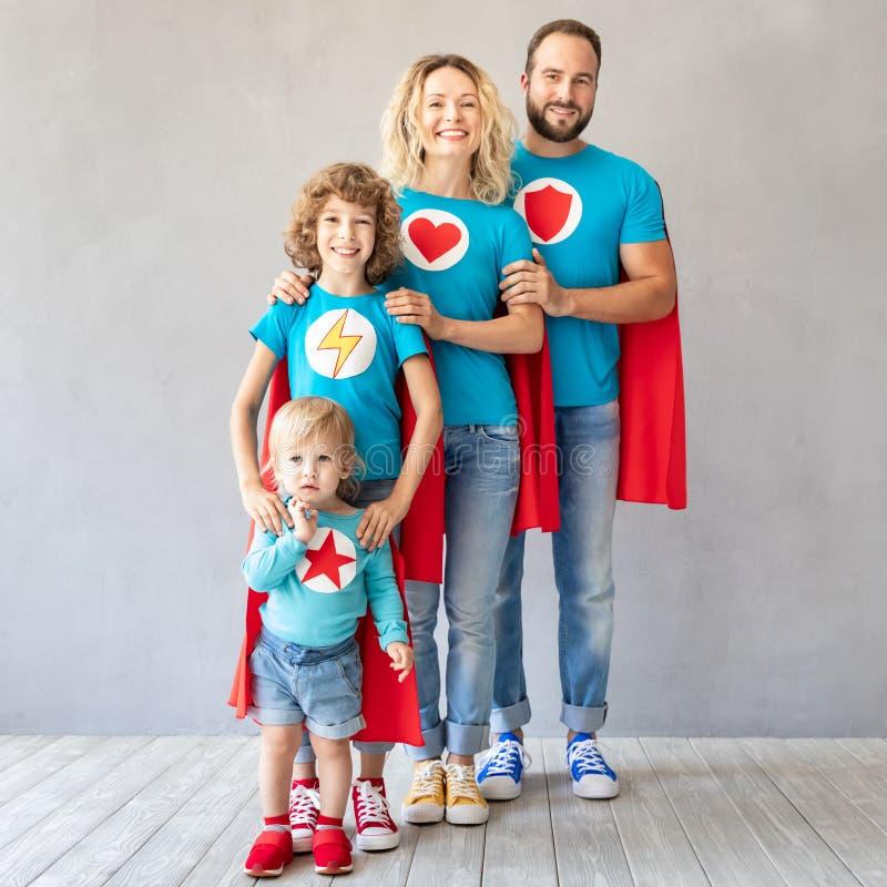 Familie van superheroes die thuis spelen stock afbeeldingen