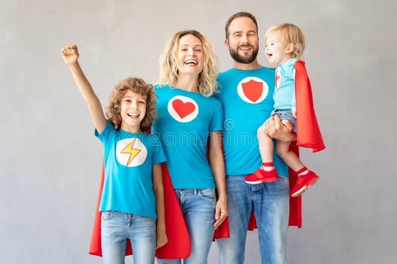 Familie van superheroes die thuis spelen royalty-vrije stock afbeelding