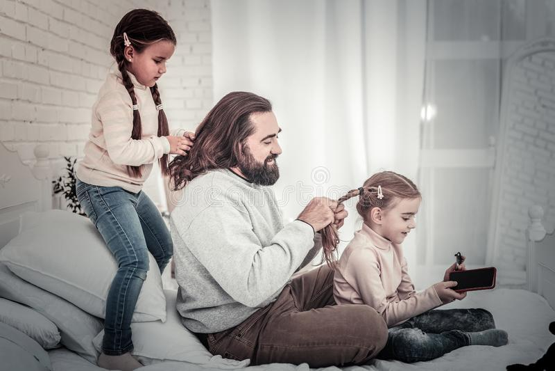 Familie van vader en twee dochters die elke anderen vlechten haar royalty-vrije stock afbeelding