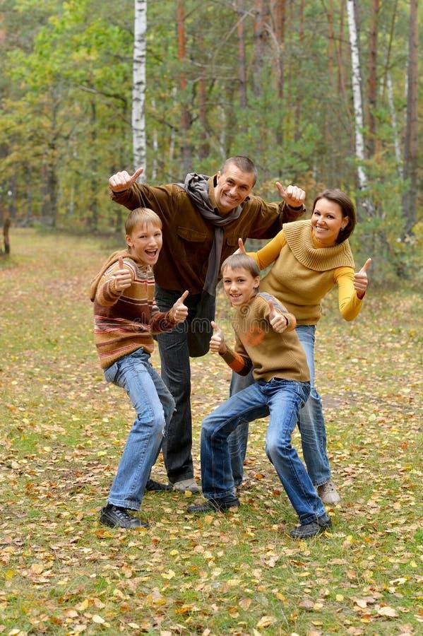 Familie van vier die duimen in bos tonen royalty-vrije stock afbeelding