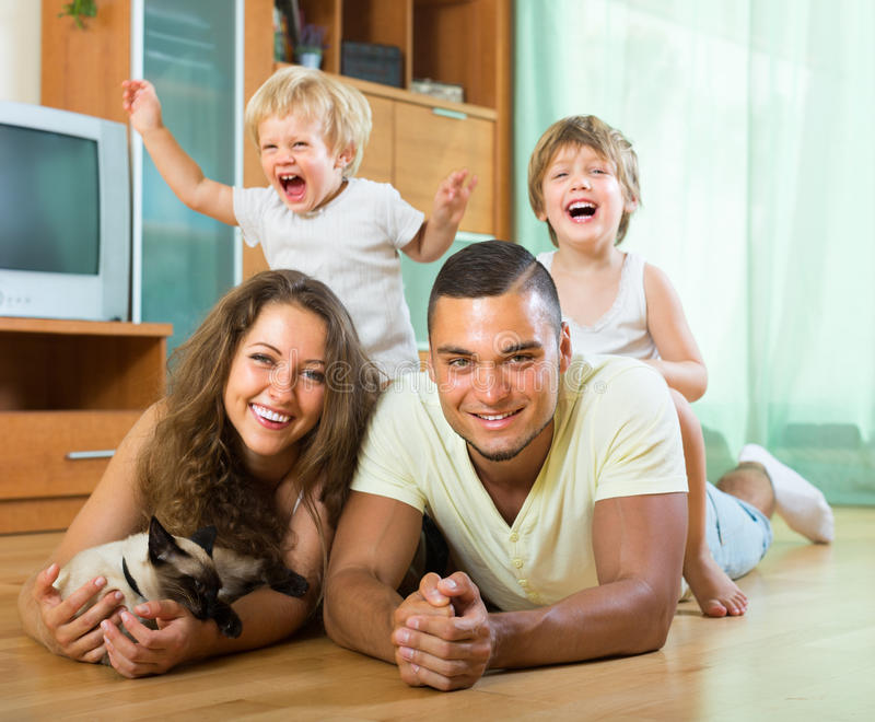 Familie van vier die met katje spelen royalty-vrije stock afbeeldingen
