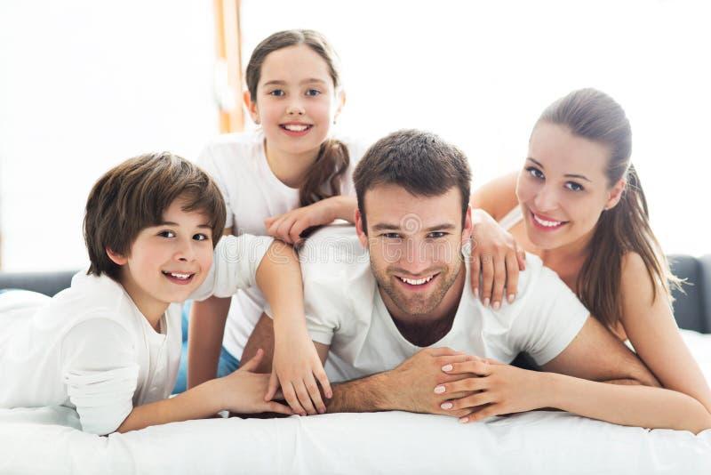 Familie van vier die op bed liggen royalty-vrije stock afbeelding