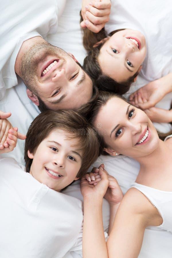 Familie van vier die op bed liggen royalty-vrije stock foto's