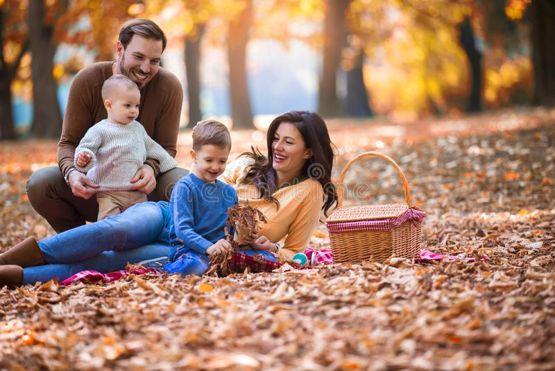 Familie van vier die pret samen in het park in de herfst hebben stock afbeeldingen
