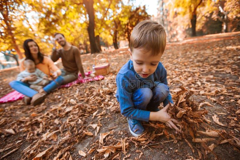 Familie van vier die pret samen in het park in de herfst hebben royalty-vrije stock foto's
